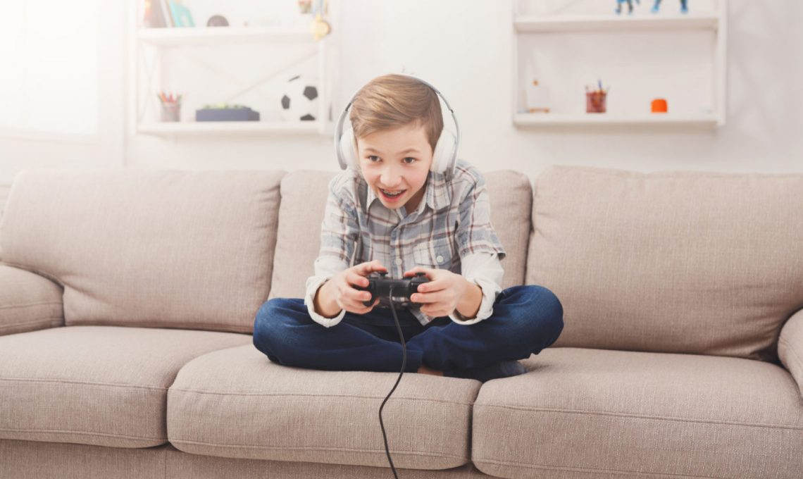 Gaming video games concept, excited boy playing football game with joystick and headphones, enjoying win while sitting on sofa in living room at home