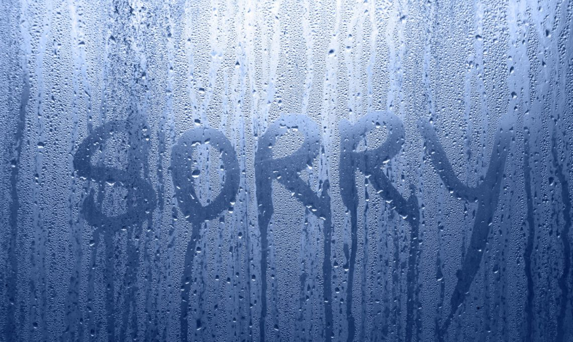 Conceptual sorry word handwritten message on the rainy glass window background. Blue color tone used.