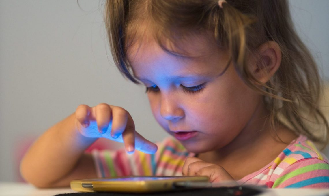 little child girl play on smartphone at home